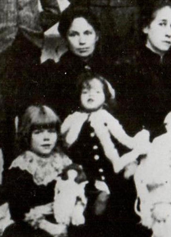 Rosalie sitting on her mother's lap in a family group photograph in 1894.
